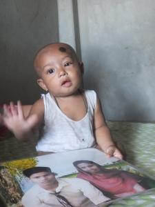 Zunayed, a nine-month old infant, plays with a photograph of his father who died in the Rana Plaza collapse last year